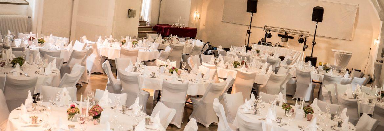Hochzeit im Kanonsaal der Wülzburg. Hochzeitsdekoration - Weiße Tische, Kerzen und Blumen.